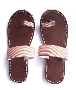 A pair of ethical dusty rose Kenyan beaded leather sandals, the Mkali sandal, on a white background