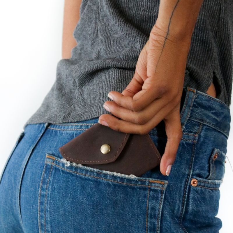 A handmade finished brown leather coin purse that empowers artisans with dignified work on the pocket of a model