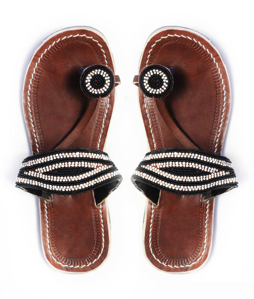 A pair of black and white ethical African beaded leather sandals, the Rafiki sandal, on a white background