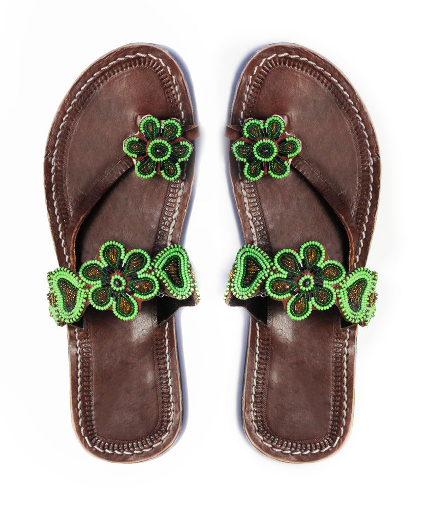 A pair of green Kenyan beaded leather sandals with flower accents, the Maua sandal, on a white background