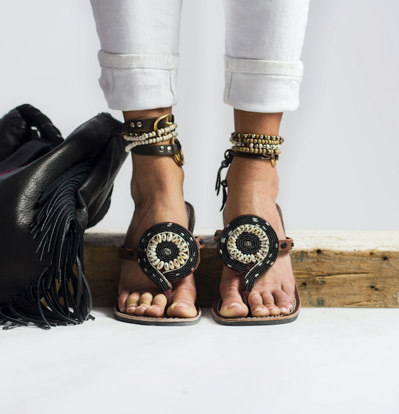 Ethical Black beaded sandals on leather with rubber roles on a model