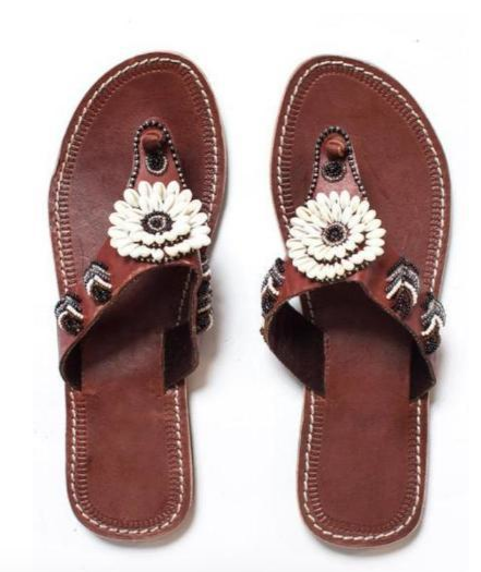 A pair of beaded leather Kenyan sandals on a white background with beading and seashells, the Malkia sandal