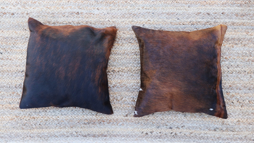 Two brown and black brindle cowhide accent pillows displayed side by side