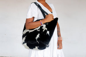 A purposeful black and white cowhide tote bag with black handles being worn by a model