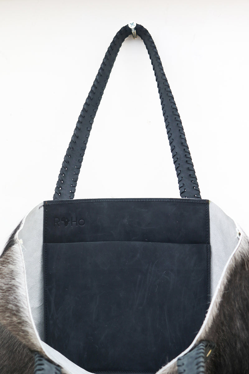 The inside pocket of a unique grey cowhide tote bag with black handles