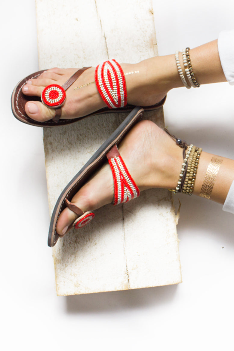 A pair of red and white African beaded leather sandals with a purpose, the Rafiki sandal, on a model