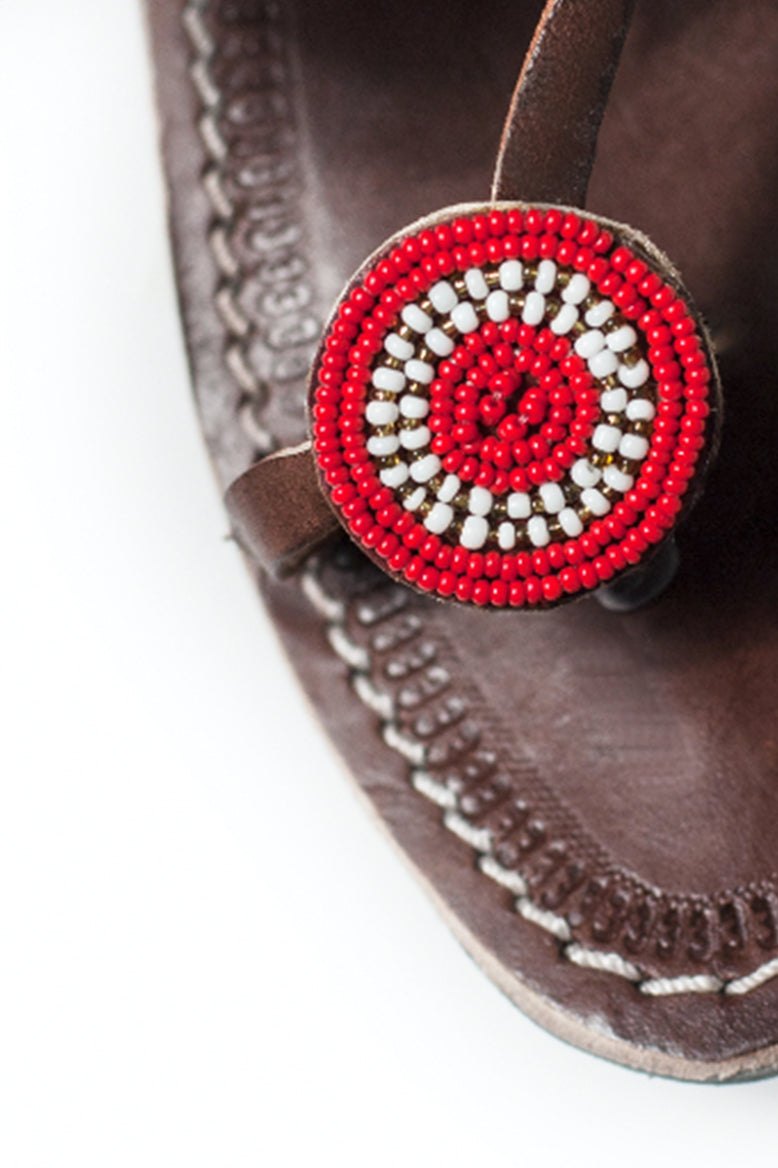 A close up of the bead word on the toe strap of a pair of red and white ethical Kenyan Rafiki Sandals