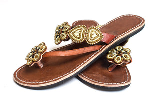 A pair of purposeful gold Kenyan beaded sandals with beaded flowers, the Maua sandal, on a white background