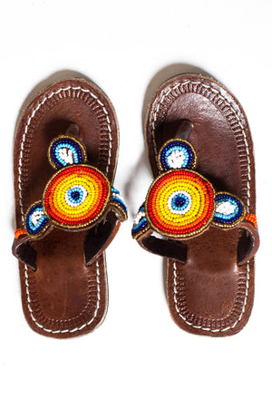 A pair of kid's sized African beaded sandals with red, yellow and blue beads