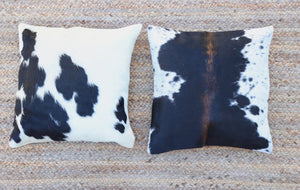 Two handmade black and white cowhide accent pillows displayed side by side