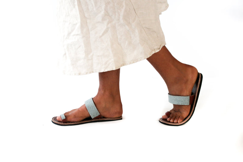 A pair of ethical grey blue Kenyan beaded leather sandals, the Mkali sandal, on a model