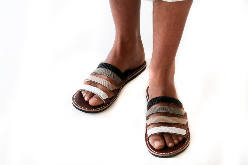 A model standing in a pair of purposeful beaded leather sandals, the Malindi Slide Sandal