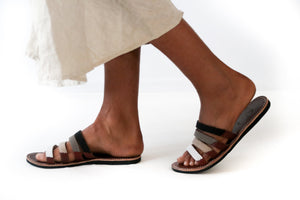 A model walking in a pair of meaningful beaded leather African sandals with four straps, the Malindi Sandal