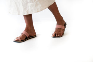 A pair of meaningful dusty rose Kenyan beaded leather sandals, the Mkali sandal, on a model