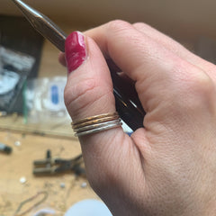 woman's hand with sterling silver and 14k gold filled thumb rings