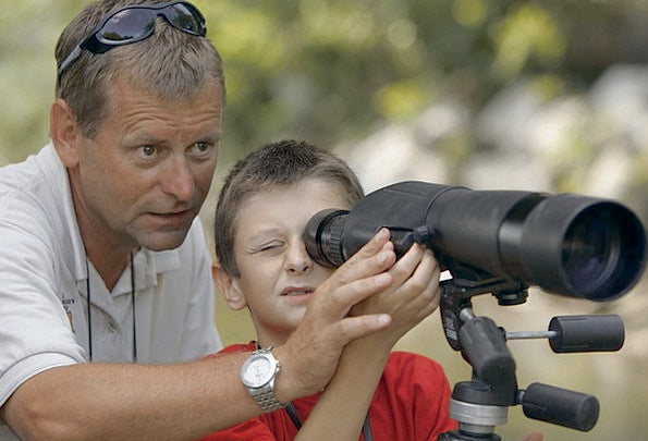 father teaching young son how to use a spotter scope