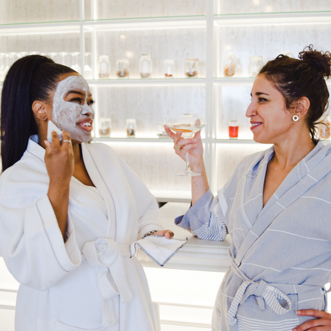 two-women-identifying-individuals-in-robes-and-face-masks-laughing-and-chatting-with martinis-in-their-hands