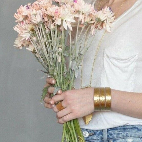 Image of model holding flowers with gold Athena Cuff by Fair Anita