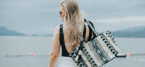 Wanderlust woman by the sea wearing the Land's End bag by Kutula Kiss