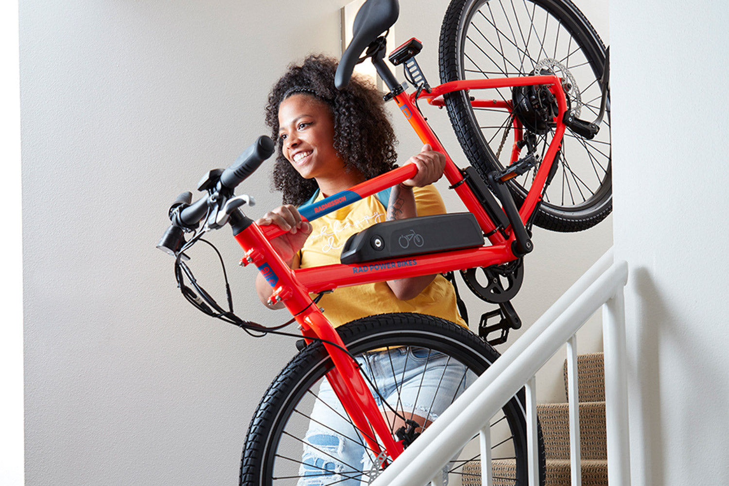 Person carrying red RadMisson e-bike down stairs