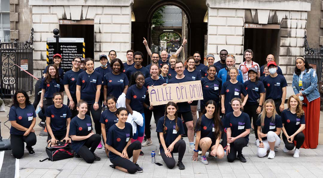 """NHS x Echelon charity ride for St Barts participants gather for a photo with sign """"Allez Omi Opi"""""""