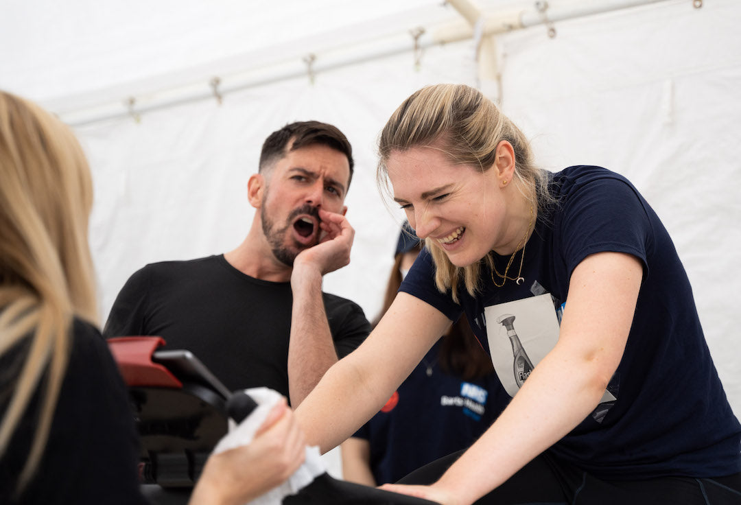 NHS x Echelon charity ride, woman rides while teammate cheers her one from behind