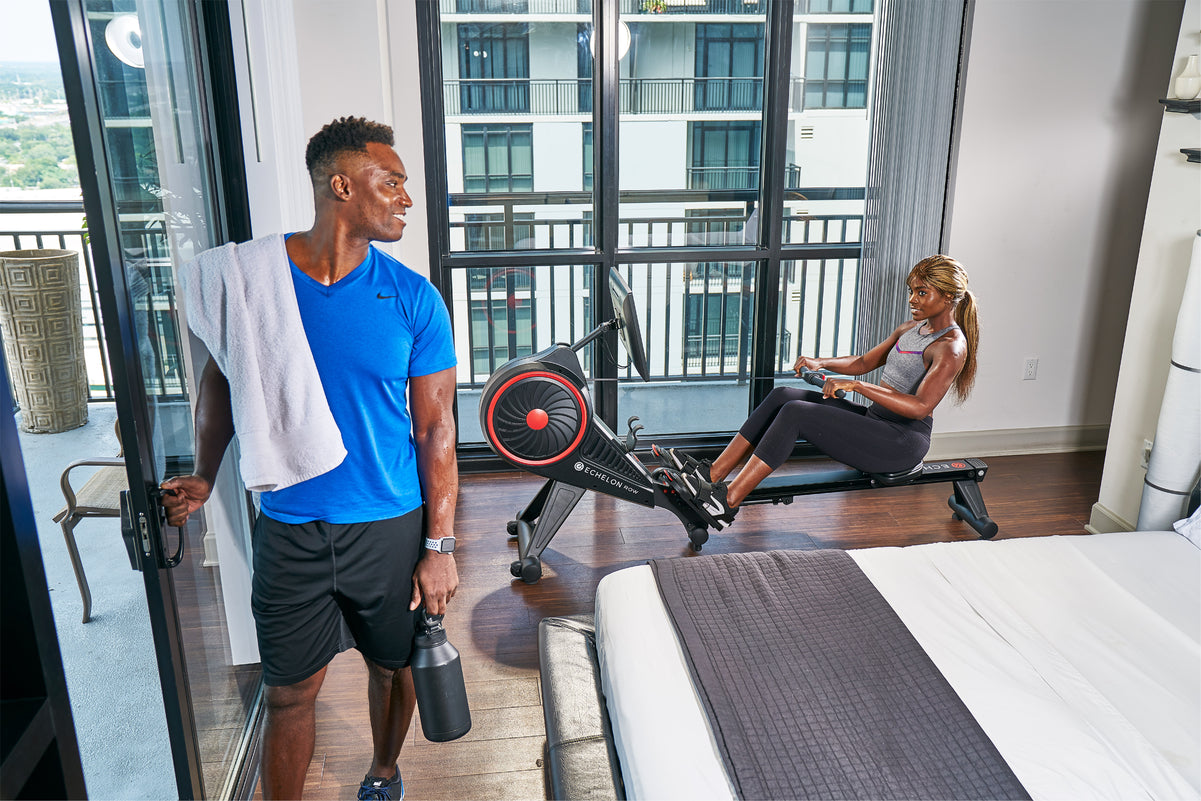 Couple working out on Row-S in their bedroom.