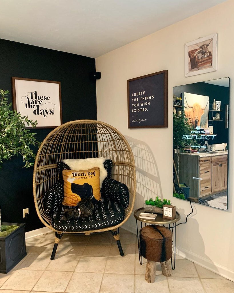 Echelon Reflect Fitness Mirror hangs on the wall in a black and gold room