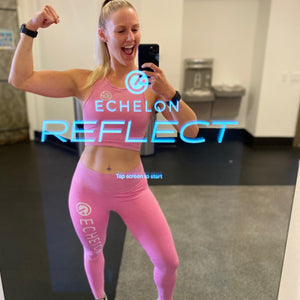 Woman flexing in the Echelon Reflect mirror