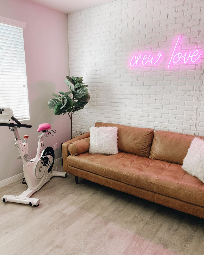 White Echelon Connect Bike with a pink next to leather couch and pink neon art