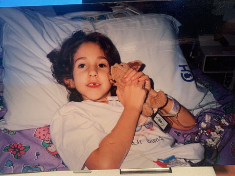 Echelon Member Melissa S. as a child in a hospital bed waiting for her first heart transplant