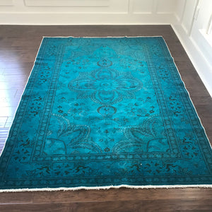 This handwoven vintage Turkish rug is overdyed with a beautiful teal and is 57 by 85 inches.