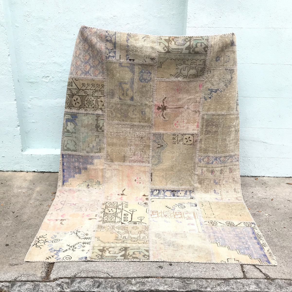 This beautiful handwoven vintage Turkish patchwork rug has a neutral background with pink, periwinkle, and teal accents. Very pretty contrast and design. 63x89 inches.