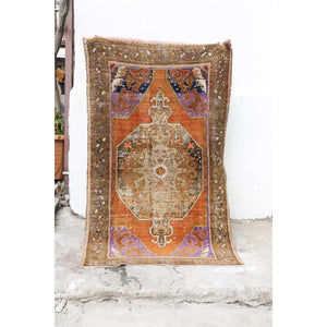 This handwoven vintage Turkish rug is has an amazing orange with purple, navy and neutral accents. Niğde.