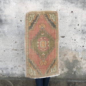 This small handwoven vintage Turkish rug has a great muted colors in a geometric design. Great for entryways, bathrooms, kitchens and layering. 19x36 inches.