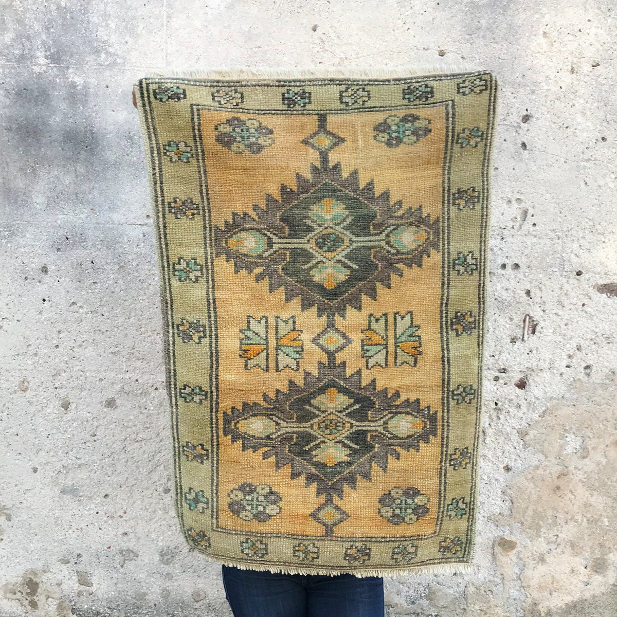 This small handwoven vintage Turkish rug has a yellow, grays and purples in a geometric design. Great for entryways, bathrooms, kitchens and layering. 22x34 inches.