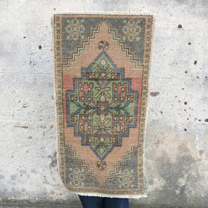 This small handwoven vintage Turkish rug has a great length and fun blush tones. Great for entryways, bathrooms, kitchens and layering. 20x37 inches.