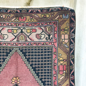 This handwoven vintage Turkish rug has a beautiful deep pink/mauve background with navy, olive, pink, and gold accents. Niğde.