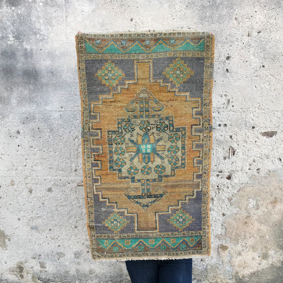 This small handwoven vintage Turkish rug has a beautiful teals, yellow, and purples. Great for entryways, bathrooms, kitchens and layering. 20x34 inches.