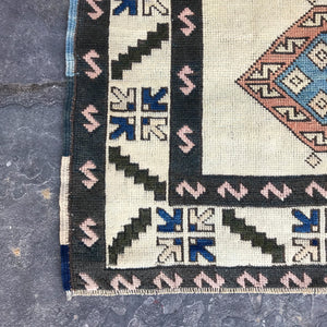 Black and white with peach and blue accents. This handwoven vintage Turkish rug has amazing colors and is around 4x6 feet.  51x72 inches.