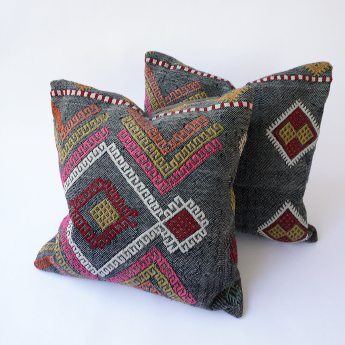 This pair of 16x16 Kilim pillowcases are cut from the same rug and made from recycled handwoven vintage Turkish kilims.  Zipper closure. Insert not included. Natural dyes. Wool.   Background color is a demin blue.  Other colors include red, white, pink, green and orange.