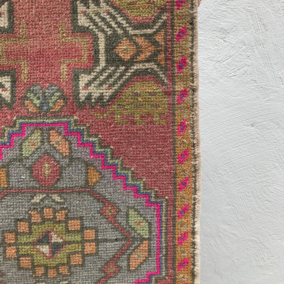 This small handwoven vintage Turkish rug has great colors including peach and pink. Great for entryways, bathrooms, kitchens and layering. 19x37 inches.