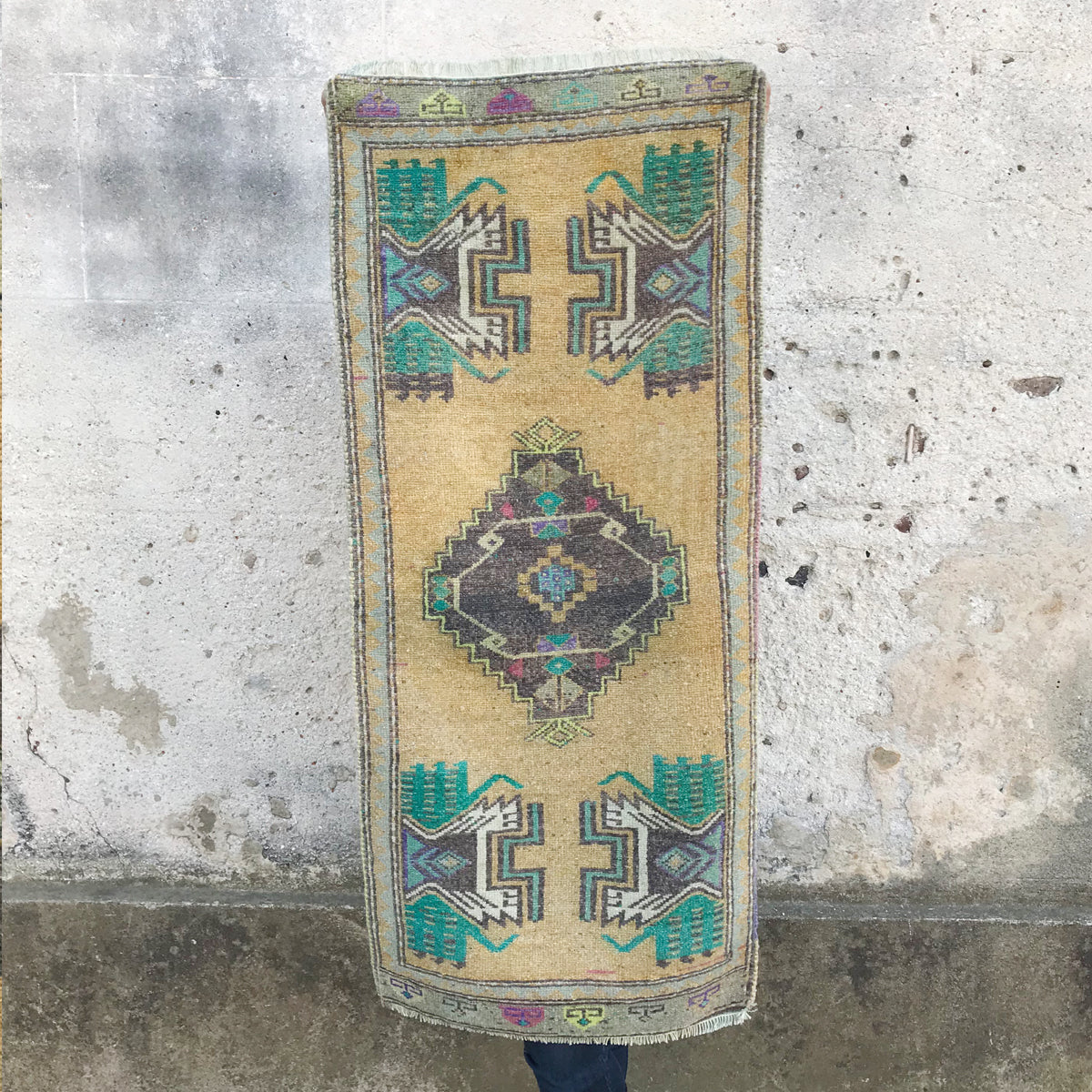 This small handwoven vintage Turkish rug has a beautiful teals, yellow, grays and purples.  Extra long for a small rug! Great for entryways, bathrooms, kitchens and layering. 20x47 inches.