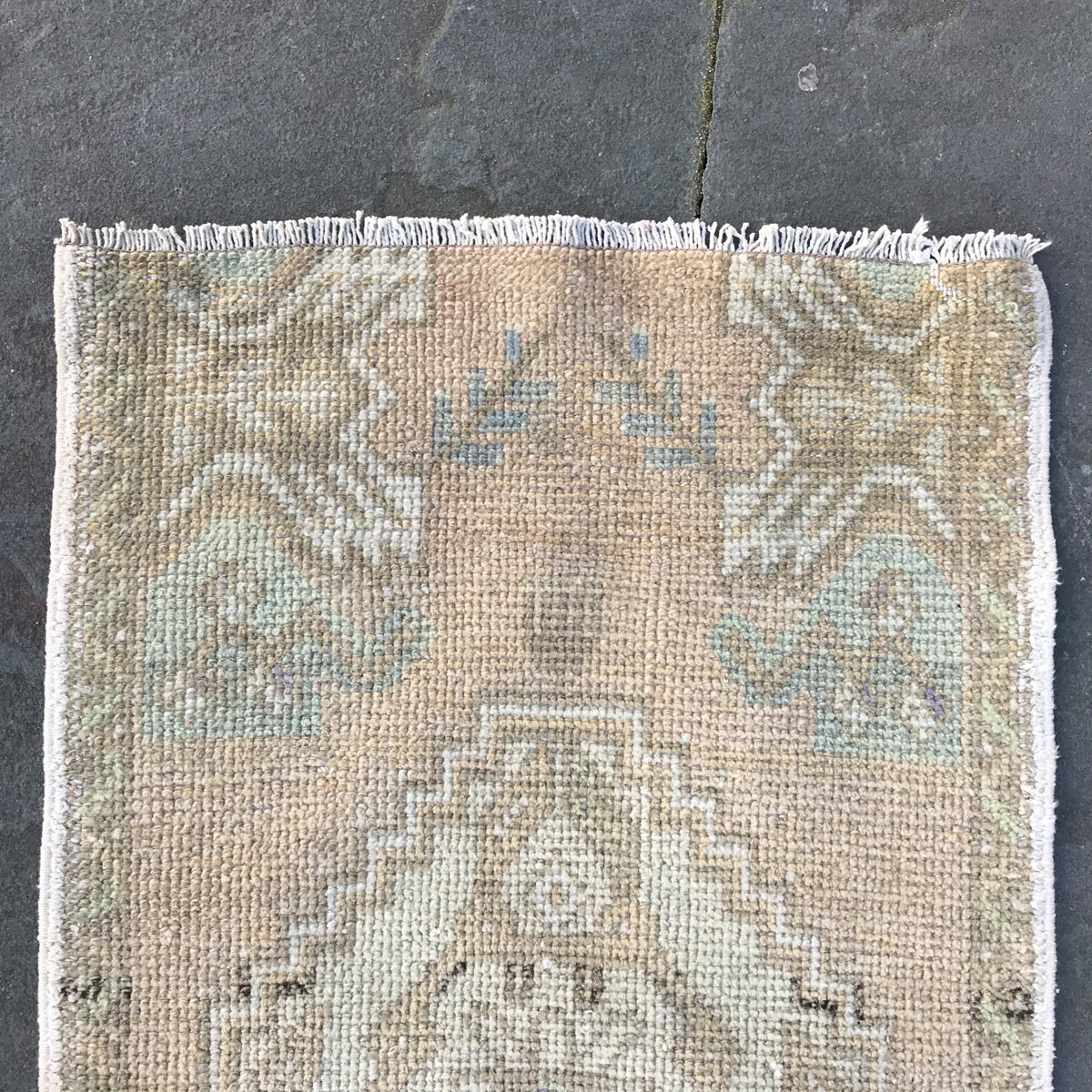 This small handwoven vintage Turkish rug has subtle hints of teals, greens, and lavender! Great for entryways, bathrooms, kitchens and layering. 19x36 inches.