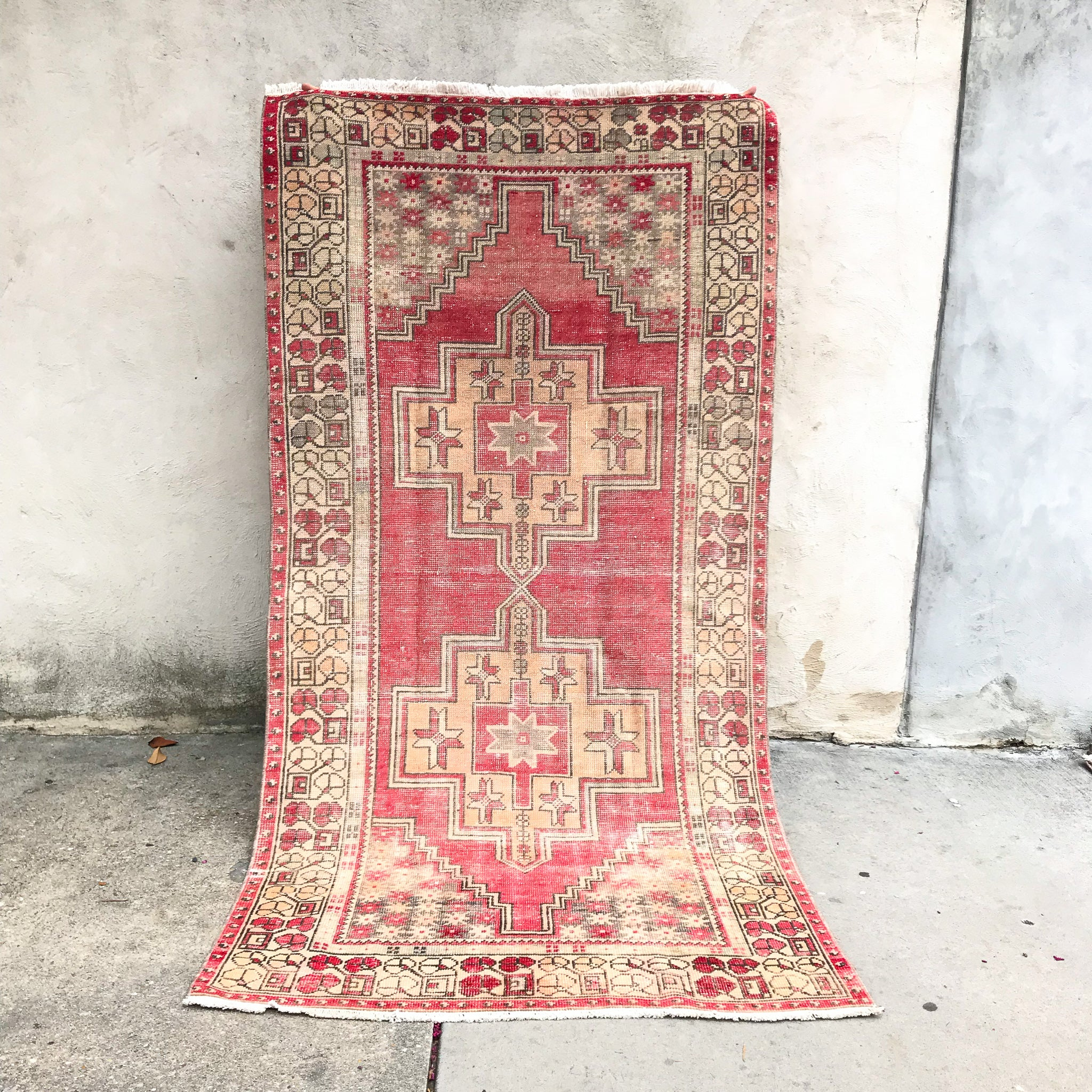 This handwoven vintage Turkish rug has beautiful neutral and light gold accents. Background color is a deep salmon pink / red. Niğde.