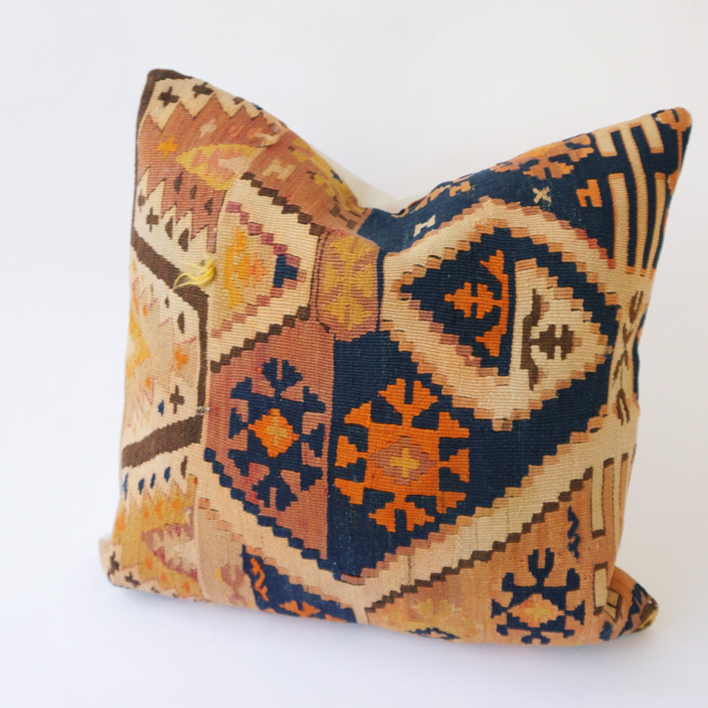 24x24 Kilim pillowcase made from recycled handwoven vintage Turkish kilims.  Zipper closure. Insert not included. Natural dyes. Wool. One of a kind.   Colors include navy, orange, yellow, brown, and tan.