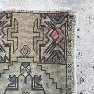 This small handwoven vintage Turkish rug has a beautiful pops of pink and purples. Great for entryways, bathrooms, kitchens and layering. 17x34 inches.