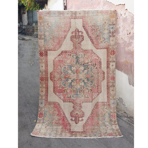 This avanoz handwoven vintage Turkish rug is has beautiful pinks and blues on a off-white background.