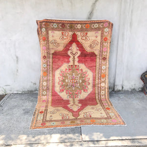 This Niğde handwoven vintage Turkish rug has an absolutely stunning pinkish red background with amazing orange and blue accents. 4'8x8'3
