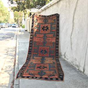 This vintage Herki Turkish runner has a beautiful shade of brown, rust and peach with blue and neutral accents in the typical Herki geometric design. 4'5x12'2